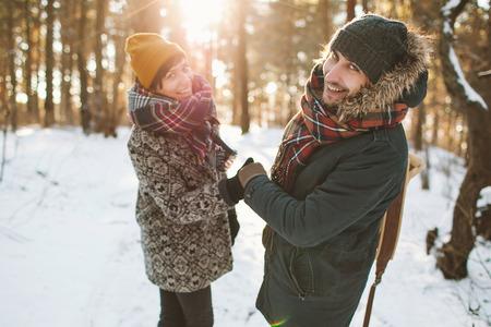 冬の森で楽しいを持っている流行に敏感な若いカップル 写真素材