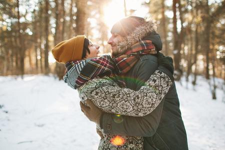 流行に敏感な若いカップルが冬の森でお互いをハグ