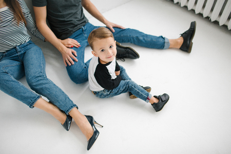 concrete floor: Young hipster father, mother holding cute baby boy on concrete floor over white background