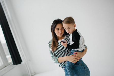 Young mother and cute baby boy with smartphone over white background