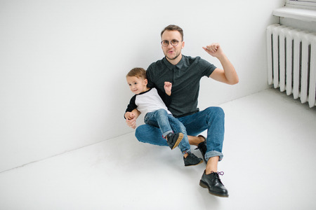 Young hipster father and cute baby boy in jeans sitting on blank floor over white background