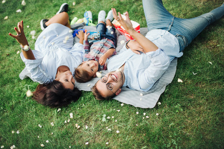 Happy young mother father and baby boy laying on grass in park outdoors with popcorn