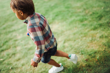 Baby boy walking in the park on green grass