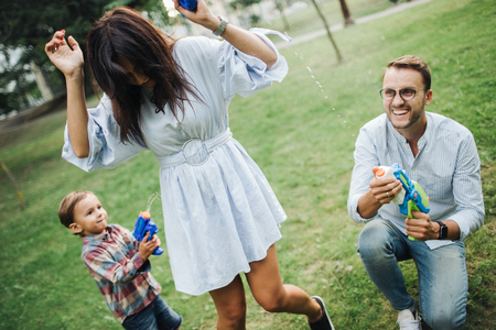Baby boy playing water guns with young hipster parents in park in summer outdoors Stok Fotoğraf