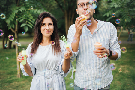 Young beautiful couple playing with bubble wands in park outdoors in summer