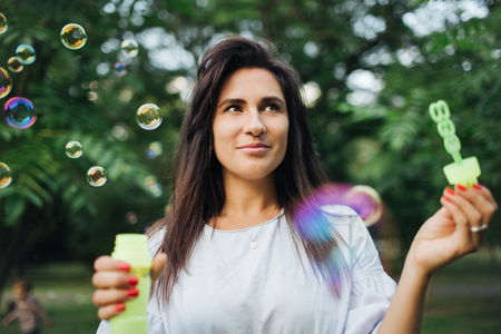 Young pretty caucasian hipster woman playing with bubble wands in park outdoors