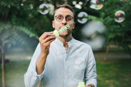Young hipster man in glasses playing with bubble wands in park outdoors