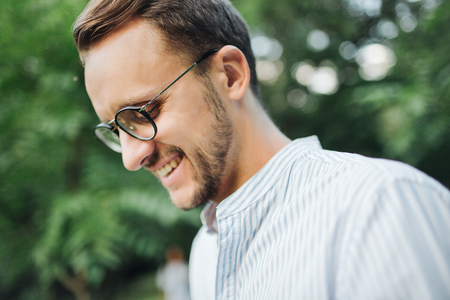 Young hipster man in glasses smiles outdoors in park