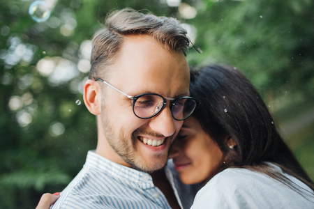 Young pretty couple embrace one another in park outdoors