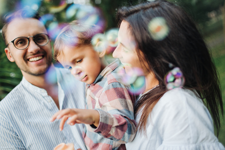 Happy young family playing with bubble wands with son in park outdoors in summer
