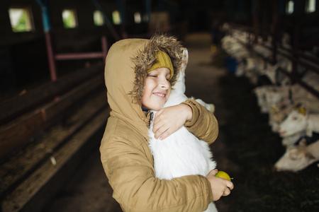 Piccolo ragazzo sveglio che abbraccia la capra sulla fattoria di formaggio di capra Archivio Fotografico - 91039417