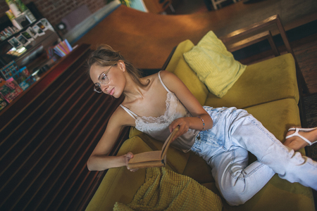 Young pretty skinny caucasian woman reading book in loft cafe wearing eyeglasses