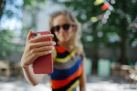 Young beautiful skinny blonde female taking selfie in colorful dress outdoors in summer Stok Fotoğraf