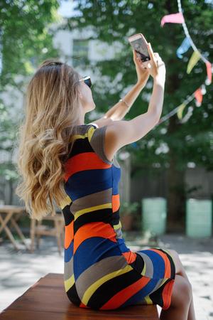 Hermosa joven rubia delgada que toma autofoto en vestido colorido al aire libre en verano Foto de archivo - 91113758