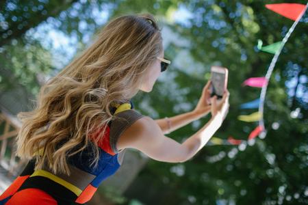 Hermosa joven rubia delgada que toma autofoto en vestido colorido al aire libre en verano Foto de archivo - 91113759