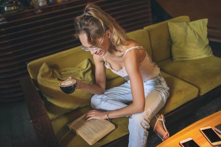 Joven bastante caucásica mujer caucásica libro de lectura en el sofá de apartamentos con anteojos Foto de archivo - 91113760