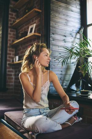 Jonge mooie vrouw, luisteren naar muziek en chatten met behulp van smartphone in café Stockfoto
