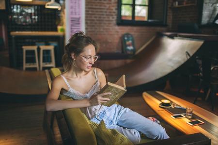 Giovane libro di lettura caucasico della donna abbastanza scarna in occhiali d'uso del caffè del sottotetto Archivio Fotografico - 91133837