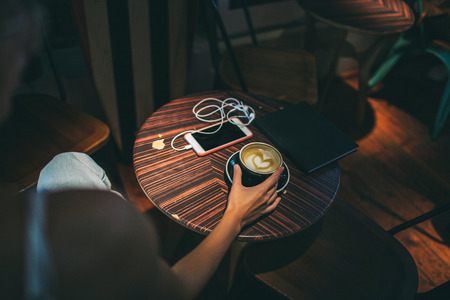 Female hand with coffee over table, smartphone and notebook indoor in cafe Foto de archivo - 91114093