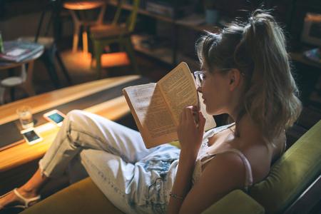 Joven bastante caucásica mujer caucásica libro de lectura en el sofá de apartamentos con anteojos Foto de archivo - 91114096