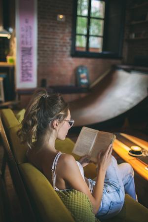 Giovane libro di lettura caucasico della donna abbastanza scarna in occhiali d'uso del caffè del sottotetto Archivio Fotografico - 91133839