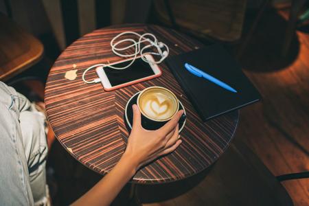 Vrouwelijke hand met koffie over lijst, smartphone en notitieboekje binnen in koffie Stockfoto