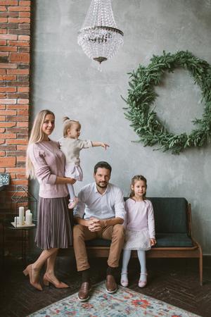 Jonge familie van moedervader en twee dochters die op bank in Kerstmis verfraaide ruimte zitten Stockfoto