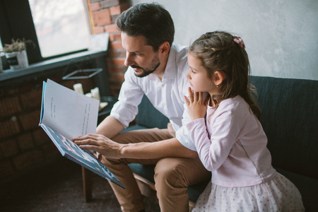 Young father reading story book to his little daughter