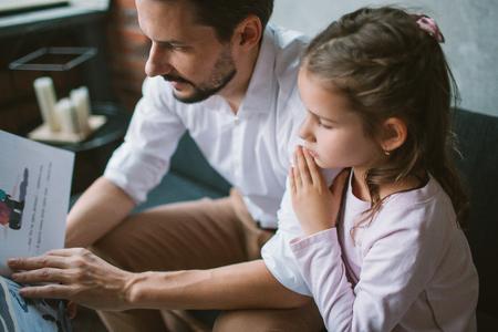 Joven padre leyendo el libro de cuentos a su pequeña hija Foto de archivo - 91981037