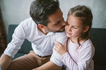 Joven padre besando a su pequeña hija y libro de lectura Foto de archivo - 92043838