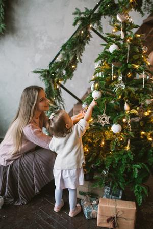 Jonge moeder die Kerstboom met weinig dochter in zolderflat verfraait