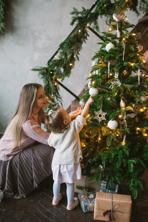 Young mother decorating Christmas tree with little daughter in loft apartment 스톡 콘텐츠