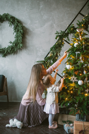 Young mother decorating Christmas tree with little daughter in loft apartment Stok Fotoğraf