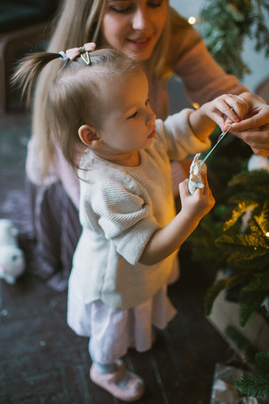 Young mother decorating Christmas tree with little daughter in loft apartment Фото со стока
