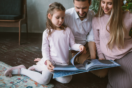 Little daughter reading book with father and mother sitting on floor at home
