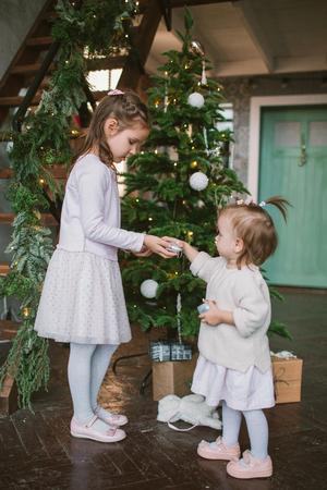 Dos pequeñas hermanas lindas decorar el árbol de navidad verde en el hogar Foto de archivo - 92043840
