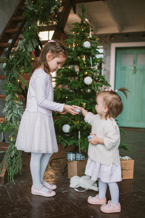 Two little cute sisters decorating green Christmas tree at home