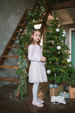 Little cute girl decorating green Christmas tree at home