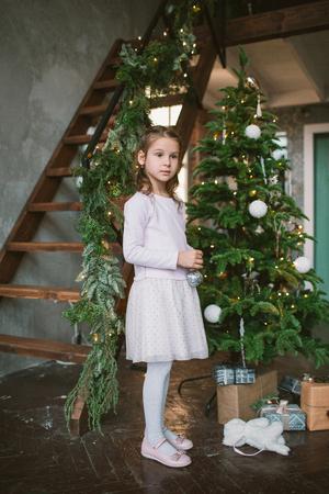 Weinig leuk meisje die groene Kerstboom thuis verfraaien