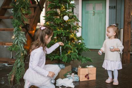 Due sorelline sveglie che decorano l'albero di Natale verde a casa Archivio Fotografico - 91943942