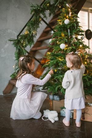Due sorelline sveglie che decorano l'albero di Natale verde a casa Archivio Fotografico - 91996153