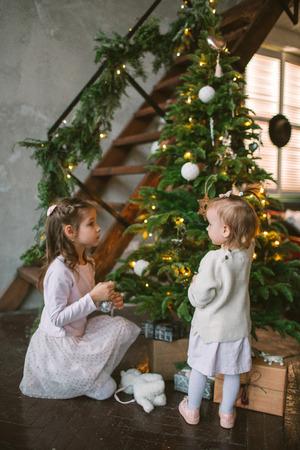 Due sorelline sveglie che decorano l'albero di Natale verde a casa Archivio Fotografico - 91981041