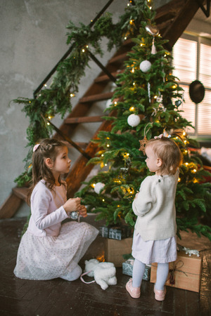 Two little cute sisters decorating green Christmas tree at home Foto de archivo - 91981041