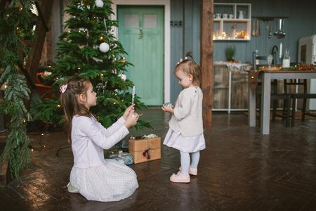 Dos pequeñas hermanas lindas decorar el árbol de navidad verde en el hogar Foto de archivo - 92043842