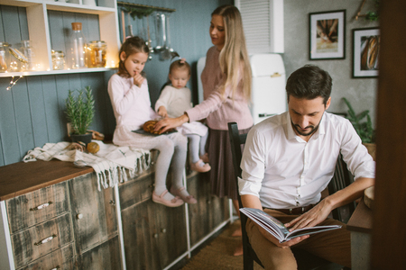 Father reading book to little daughters and wife in Christmas decorated kitchen Фото со стока