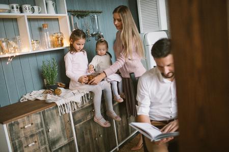 Vader leesboek voor kleine dochters en echtgenote in de kerst versierde keuken