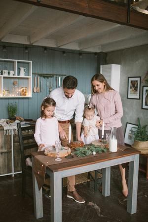 Jonge ouders en kleine dochters met taart vieren Kerstmis op ingerichte keuken Stockfoto