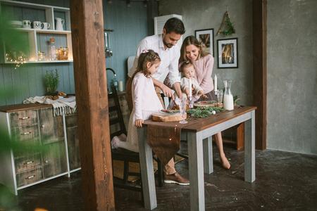 Giovani genitori e piccole figlie con la torta che celebra il Natale sulla cucina decorata Archivio Fotografico - 91981044