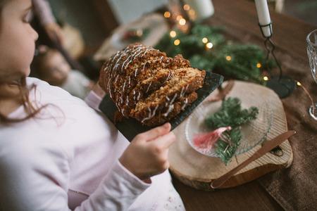 Weinig babymeisje met Kerstmiscake op het keuken binnen vieren