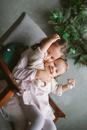 Schattige kleine zusters zittend op een stoel in Kerstmis ingericht kamer